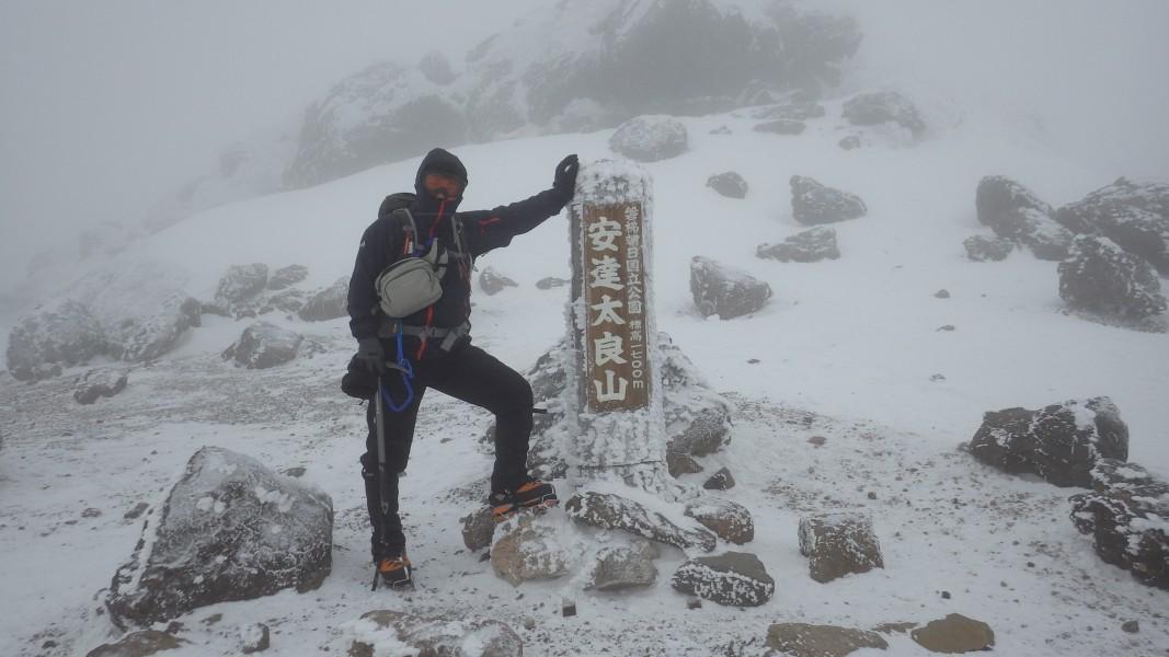 安達太良山山頂の肩にある標柱。三角点は背後の岩場の上。
